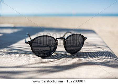 Female sunglasses on a sun lounger with defocused sand beach and sea on the background