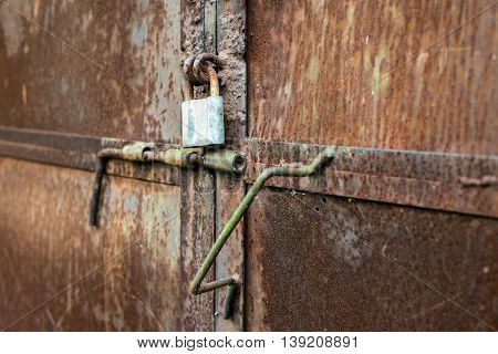 Old rusty metal door with a padlock