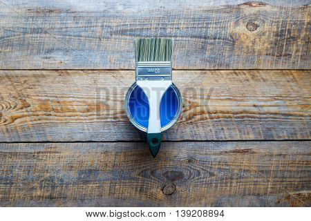 painting with open can of blue paint and white brush on wooden background top view
