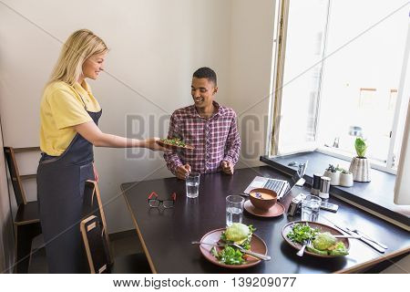 Handsome man is being served in vegan restaurant or cafe. Blond waitress lady giving her guest vegan salad. Vegan concept.