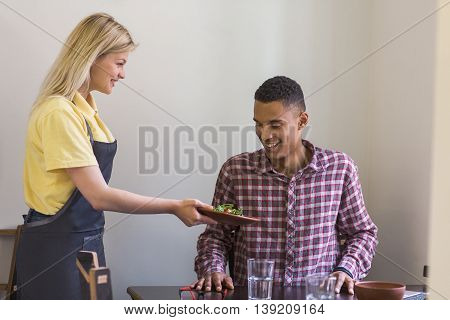 Vegan and healthy food concepts. Blond waitress lady giving her guest vegan salad. Handsome man is being served in vegan restaurant or cafe.