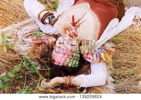 Fashion boho style woman portrait, enjoy summer lying on a hay, sunny day outdoor