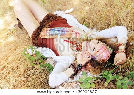 Dressed in boho chic style woman lying on a hay, sunny day outdoor, healthy and happy lifestyle concept