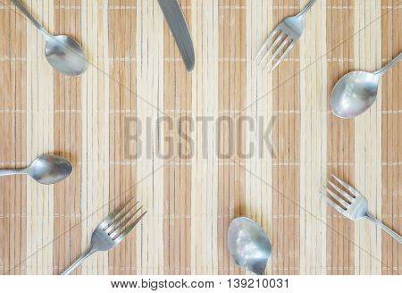 Closeup group of stainless fork spoon and knife on wood mat textured background with copy space at the center in top view