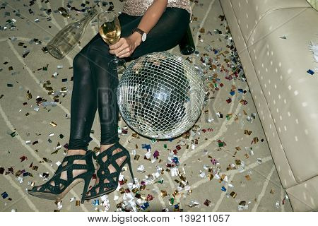 Cropped image of party woman lying on floor next to disco ball