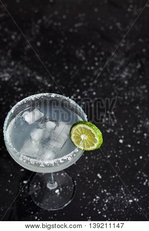 Classic mexican margarita cocktail on black background. Margarita glass full of ice, salt and lime on side. Black background with white sea salt spots.