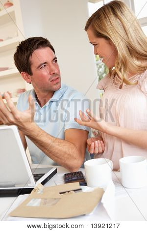 Young couple discussing their finance over laptop computer