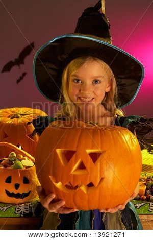 Halloween party with a child holding carved pumpkin