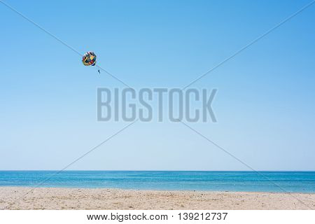 Parasailing summer sport. Parachute and boat. High in the sky over the sea.