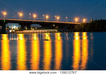 Night bridge lights reflected in river water