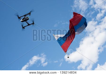 St. Petersburg Russia - June 4 2016: Drone using a homemade device lifted high into the sky Russian flag.