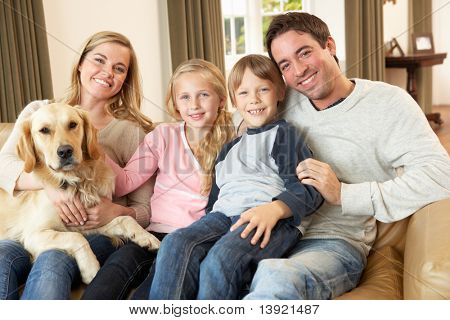 Happy young Family sitting on Sofa hält einen Hund