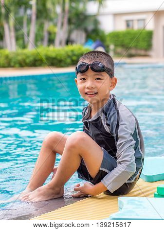 little asian boy in swimming suit with goggles