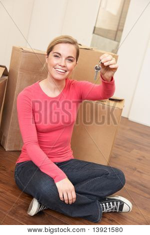 Young woman sits on the floor around boxes holding a key in her hand