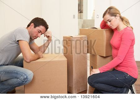 Young couple looking upset among boxes