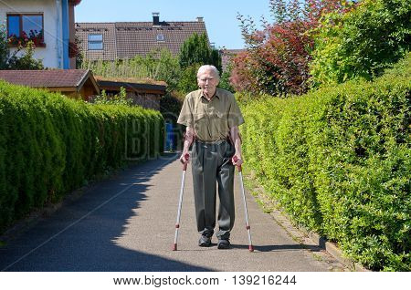 Senior retired man walking on crutches on a walkway between green hedges in a residential suburb approaching the camera front on