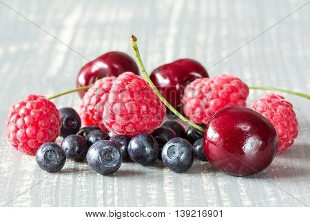 Close-up pile of summer berries on wooden background