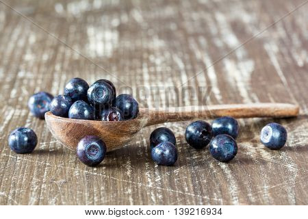 Studio macro of blueberries on an old wooden spoon