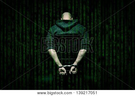 Internet criminal arrested and in handcuffs with head bowed