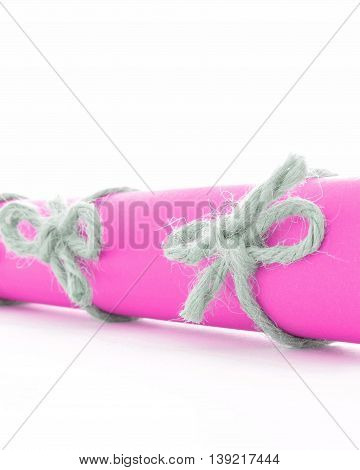 Natural handmade cord knots tied on pink message scroll, isolated