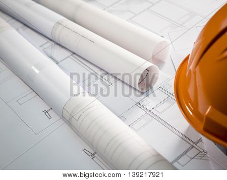 Architect rolls and plans technical project drawing on the table (Selective focus)