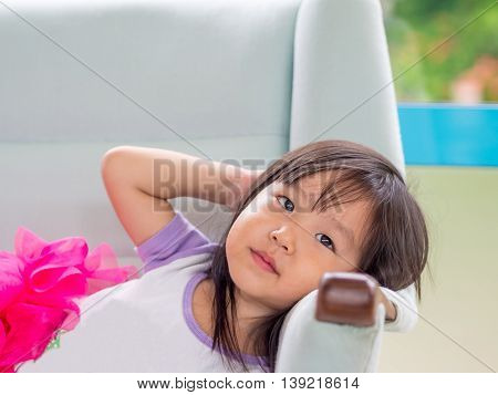 Beautiful young girl child laying down on a white sofa at home asian girl