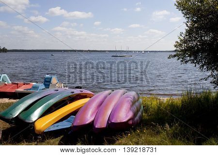 Canoes In A Coast In Front Of A Lake Full Of Sail Boats