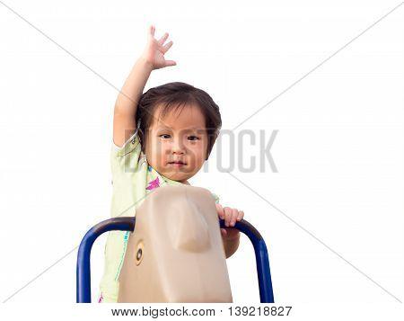 Little asian child having fun on carousel outdoors