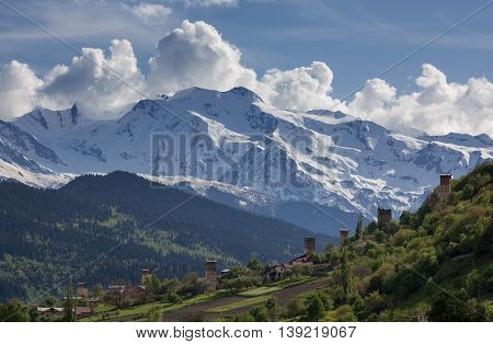 landscape, with Svan watchtowers and agricultural fields on the background of snow-capped mountain peaks and clouds, Svaneti, Georgia