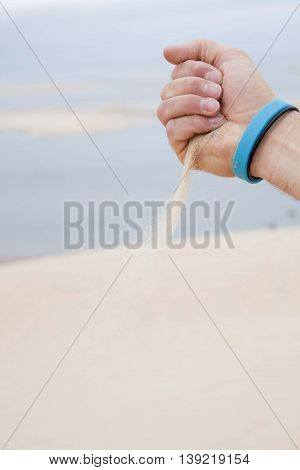 Man Hand Releasing Sand Over A Beach To Pile It