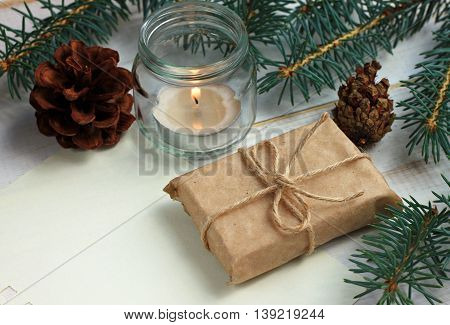 Handmade simple winter holiday decor, tea candle light in glass jar, pine boughs and cones, handcrafted gift wrap idea, empty note paper. Toned.