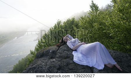 Portrait of thoughtful young bride in a white wedding dress  lying on the rocks alone with eyes closed. River in fog on background.