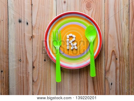 white pill on colorful dish, soft vintage tone concept for overeating medicine