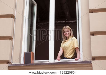 Picture of happy lady looking from window and smiling to camera. Business lady working for real estate agency. Real estate concept.
