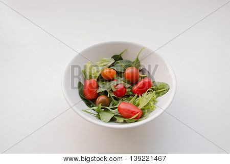 Bowl Of Cherry Tomatoes And Leafy Salad Greens