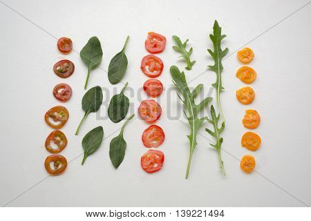 Three Types Of Cherry Tomato Slices With Baby Spinach And Roquette (arugula) Leaves Forming A Decons