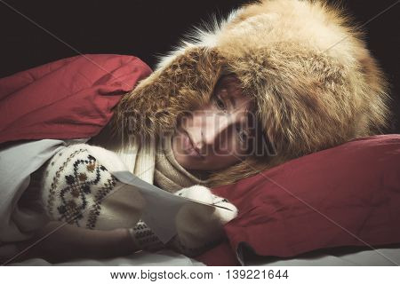Woman lying in a bed wearing fur hat and mittens looking to the photo.