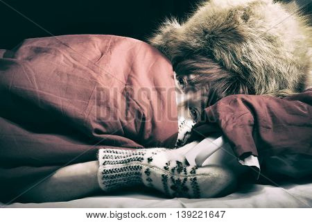 Woman lying in a bed wearing fur hat and mittens hide a mug under the pillow.