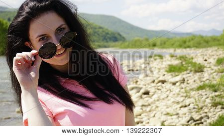 Brunette long hair lady in sunglasses wposing on the mountain river background.