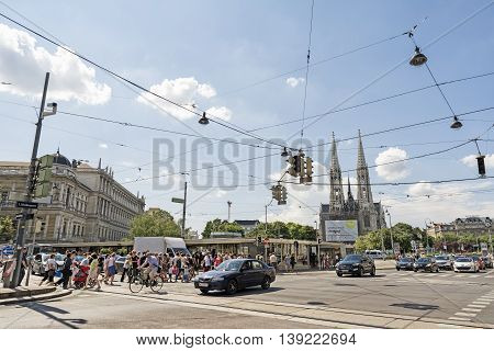 VIENNA, AUSTRIA, JULY 2,2016: Pedestrian and automobile traffic near the Schottentor metro station, Votive Church can be seen at the background.