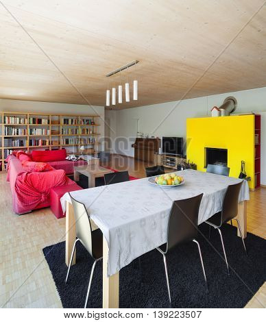 Interior of an eco house, living room with dining table and fireplace