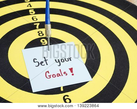 Handwriting Set your goal on notepaper with dart arrow and dart board. (Business concept)