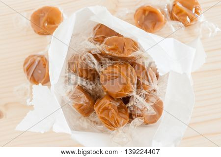 Wrapped toffee pieces in a paper sweet bag top down view