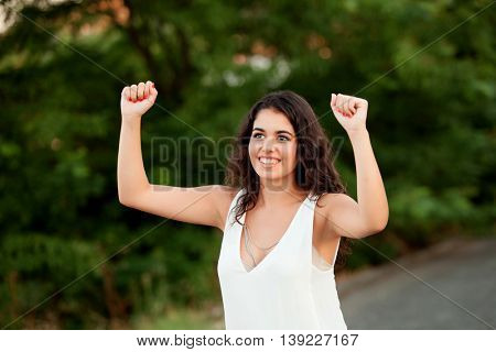 Beautiful brunette girl celebrating something in the park wiht many plants of background