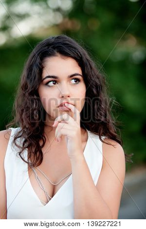 Pensive beautiful brunette girl relaxing in the park wiht many plants of background