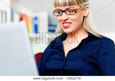 Woman sitting in front of a bookshelf using her telephone, working with a laptop in the internet from home, she is a telecommuter