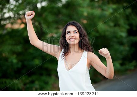 Beautiful brunette girl celebrating something in the park withmany plants of background