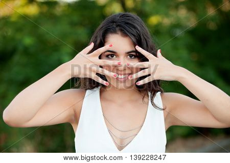 Beautiful brunette girl covering her face in the park with many plants of background