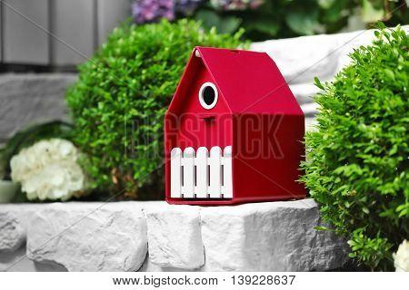 Beautiful birdhouse on stone in garden