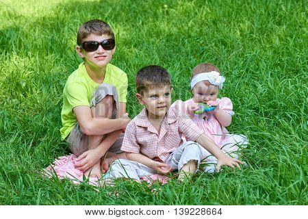 Three children sit in grass, playing and having fun.